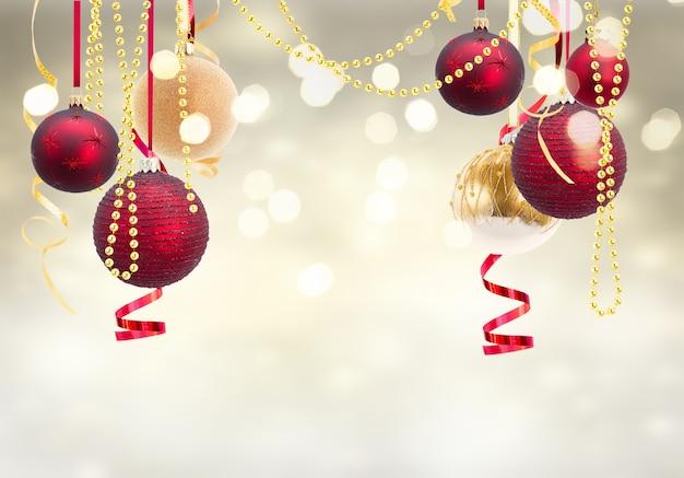 Красные и золотые новогодние шары-гирлянды на праздничном светящемся золотом и серебряном фоне