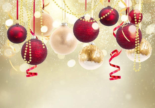 Красные и золотые новогодние шары-гирлянды на праздничном светящемся золотом фоне