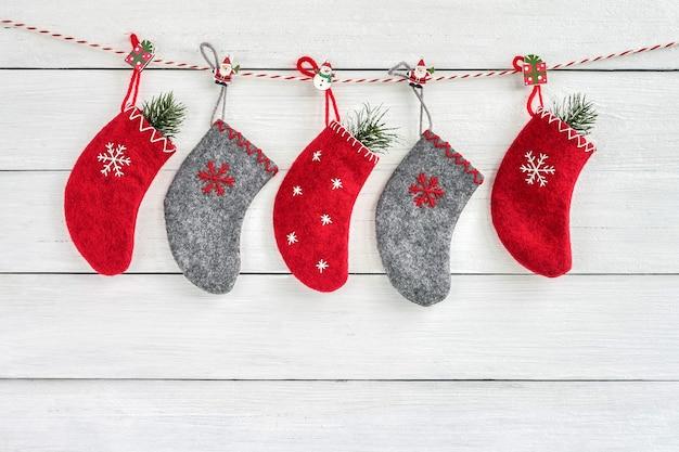 흰색 나무 바탕에 빨간색과 회색 크리스마스 양말. 크리스마스 인사말 카드입니다. 복사 공간