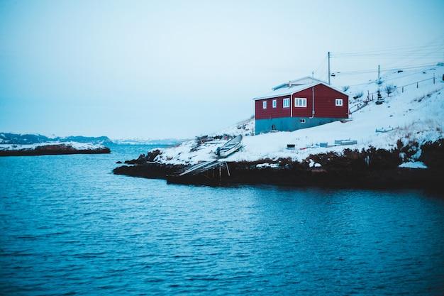 雪で覆われた水の体の近くの赤と灰色の家