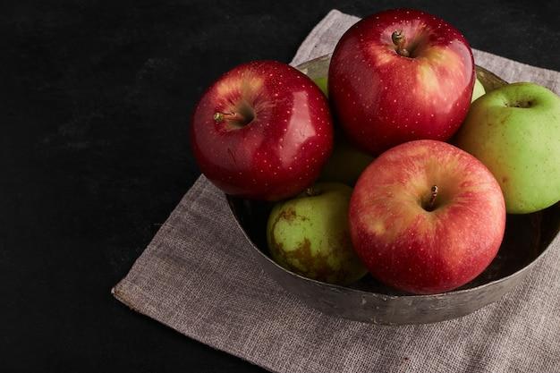 金属製のボウルに赤と緑のリンゴ、上面図。