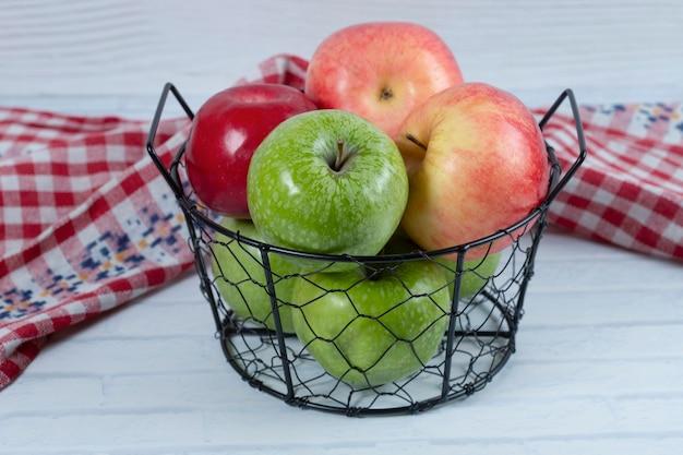 白い背景の上に置かれた金属の黒いバスケットの赤と緑のリンゴ。高品質の写真