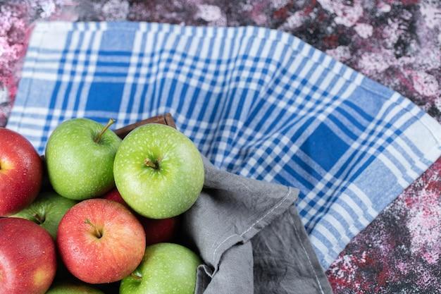 파란색 체크 수건에 고립 된 빨강 및 녹색 사과.