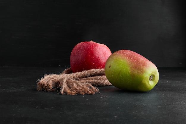 真ん中の黒の背景に赤と緑のリンゴ。
