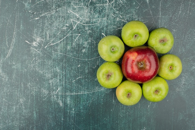 Красные и зеленые яблоки на мраморном столе.