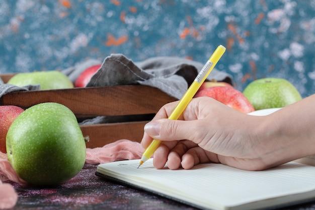 Красные и зеленые яблоки на столе с пустой книгой рецептов.