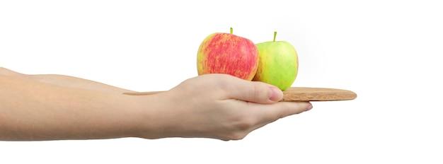 白の背景、バナー写真に分離された女性の手で木の板に赤と緑のリンゴ
