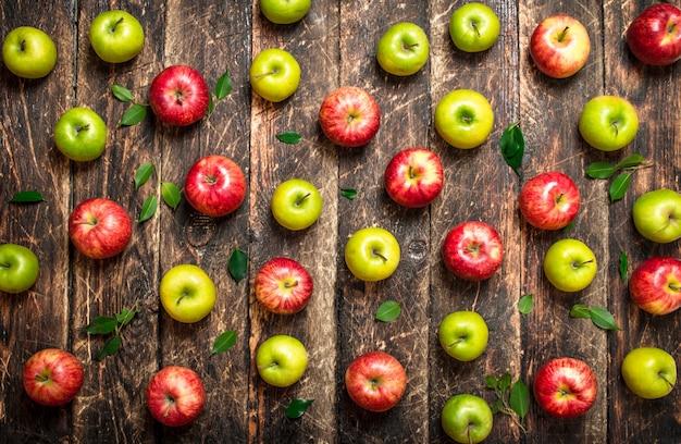 赤と緑のリンゴ。木製のテーブルの上。