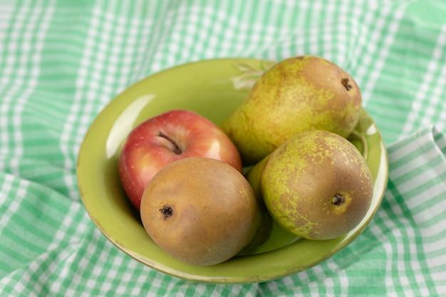 녹색 그릇에 신선한 배와 빨강 및 녹색 사과.