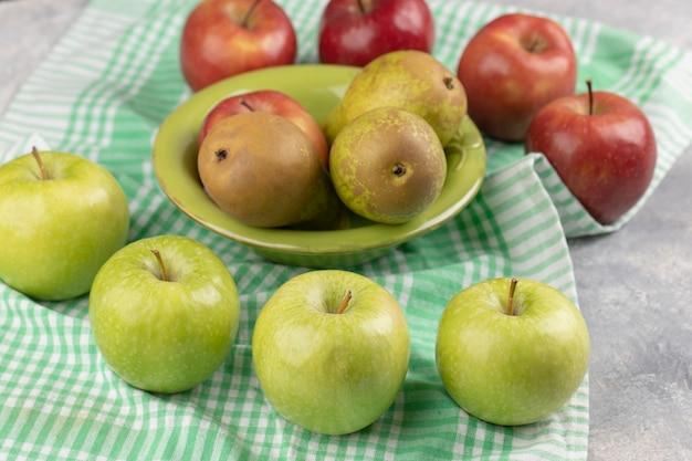 Красные и зеленые яблоки со свежей грушей в зеленой миске.
