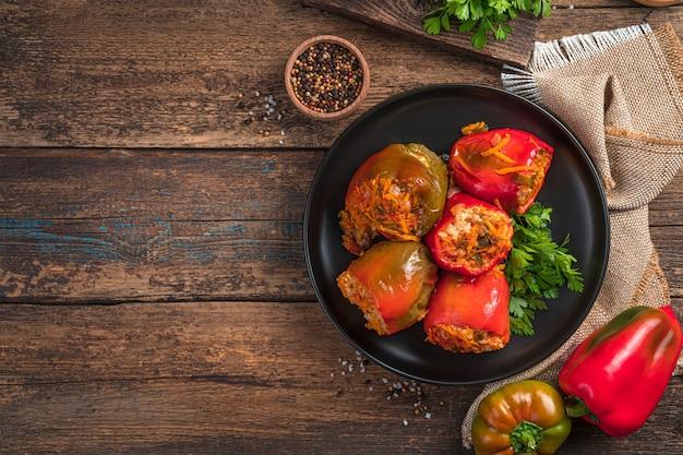 木製の背景に黒いプレートに肉とご飯を詰めた赤と緑のピーマン