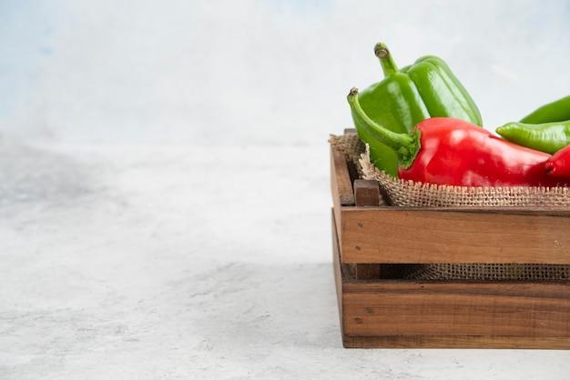 Красный и зеленый перец чили в деревянном подносе.