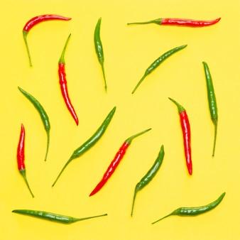 黄色の背景に赤と緑の唐辛子。明るいフードパターン。上面図、フラットレイ