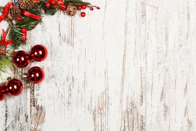 Красные и зеленые рождественские украшения на изношенном бело-коричневом деревянном столе