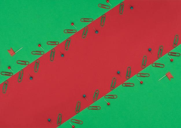 Красные и зеленые зажимы и булавки на двойном зеленом и красном фоне