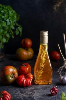 Красные и зеленые вкусные помидоры на темном столе и бутылка оливкового масла. фото высокого качества