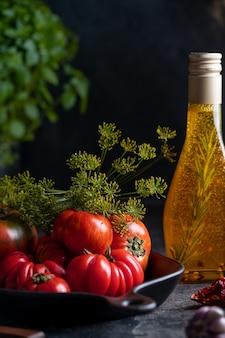 Красные и зеленые вкусные помидоры на темном столе в тарелке и бутылке с оливковым маслом. фото высокого качества