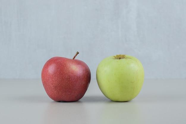 灰色の壁に赤と緑の新鮮なリンゴ。