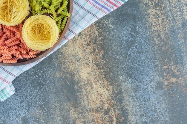 大理石の背景に、タオルの上のボウルに薄いスパゲッティと赤と緑のフジッリパスタ。