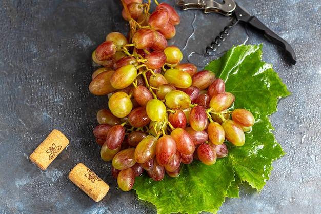 Красный и зеленый виноград на зеленом листе