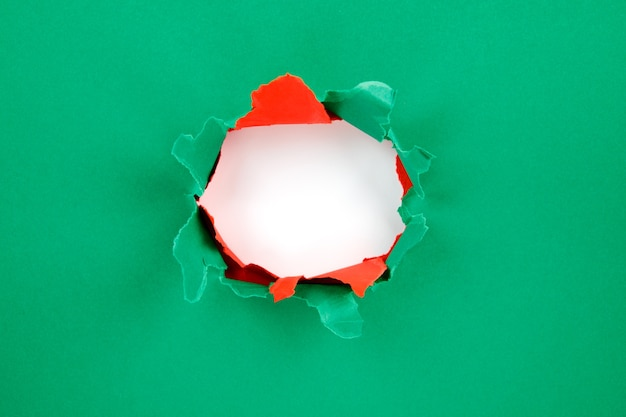 종이에 빨간색과 녹색 구멍이 찢어진면. 크리스마스 배경