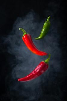 Красный и зеленый острый перец чили левитация в воздухе с дымом на черном фоне.