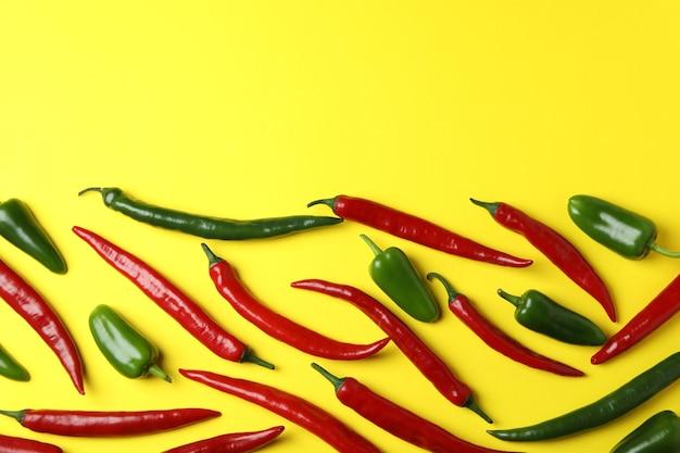 Красный и зеленый острый перец на желтом фоне