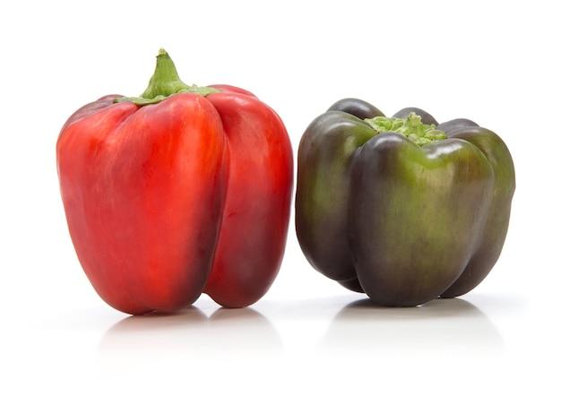 Красный и зеленый перец, изолированные на белой стене