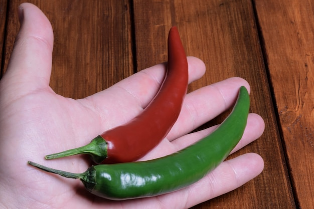 赤と緑の唐辛子のさやは、木製の茶色のテーブルの背景にある手のひらの上にあります。
