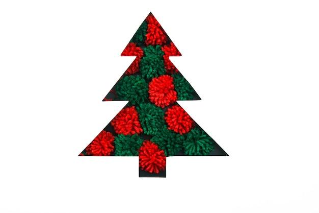 Красные и зеленые помпоны в вырезанной бумаге в форме елки для рождественской открытки или нового года