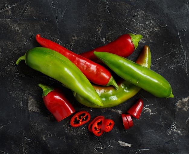 暗い背景に赤と緑のピーマン