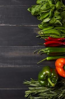 黒の木製の背景に赤と緑の野菜-ピーマン、唐辛子、ローズマリー、バジル、グリーンピースの鞘。健康食品の上面図。