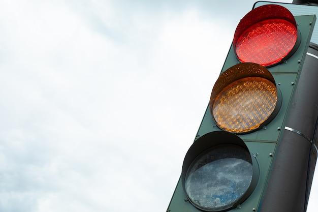 市内の信号機の赤とオレンジのライト