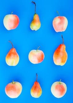 Красные и грушевые фрукты на синем фоне
