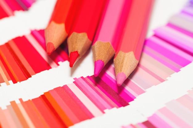 빨간색과 분홍색 색연필과 모든 색상의 컬러 차트