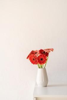 台所のテーブルと白い壁の背景に白い花瓶の赤とピンクのガーベラデイジー