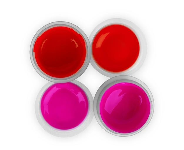 白い背景の上の瓶に赤とピンクの絵の具