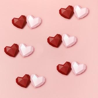 赤とピンクの多角形の紙のハートがクリーム色の表面に一緒に。バレンタインデーのコピースペースを持つ休日の背景。