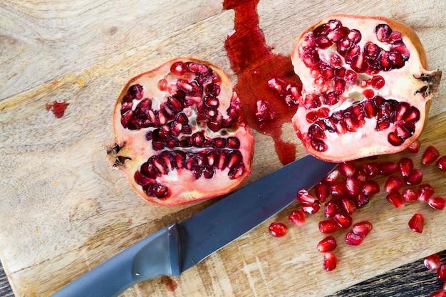 赤粒の赤く熟したフルーツザクロ、赤い種子でいくつかの部分に分割された美味しくて健康的なザクロ、新鮮なザクロのクローズアップ Premium写真