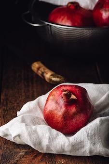 Красные и спелые плоды граната в деревенской обстановке