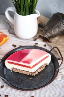 オレンジを詰めた赤と白のケーキ。黒いテーブルの近くには、オレンジ、ナッツの材料があります。素朴なスタイル。