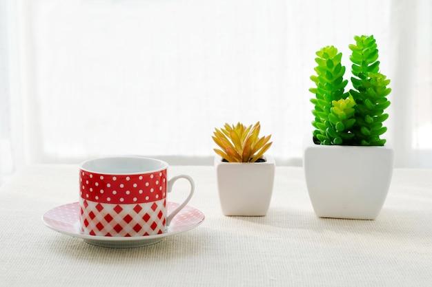 빨간색과 흰색 커피 컵과 화이트 패브릭 식탁보 배경에 작은 나무 냄비