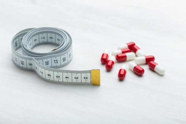 Красные и белые таблетки для похудения лежат на белом столе рядом с измерительной лентой. понятие о похудании с помощью лекарств.