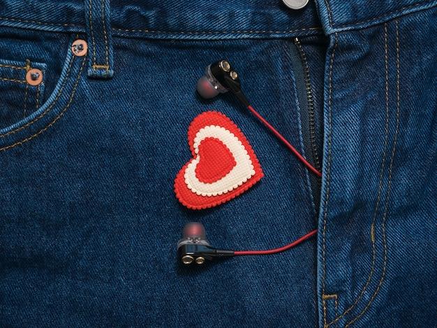 ズボンのブルージーンズからヘッドホンが突き出ている赤と白のハート。ファッショナブルな服のロマンチックなスタイル。