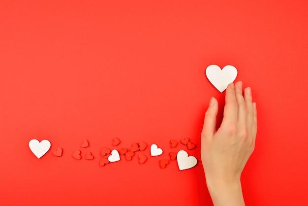 Красные и белые сердца на красном фоне. женщина, держащая белое сердце. скопируйте пространство.