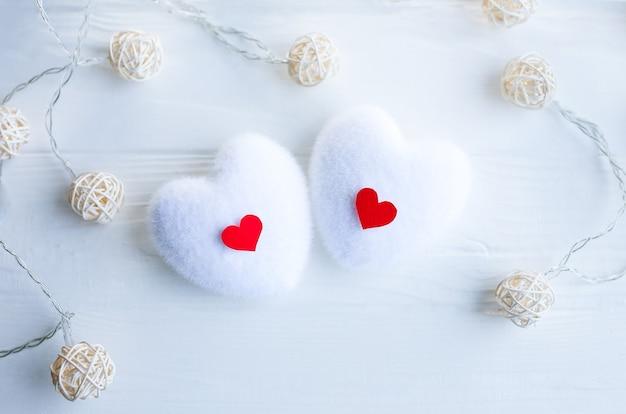 木製の背景に赤と白のハート。聖バレンタインデーのコンセプト。愛とロマンチックな写真。休日のはがき。小さな素朴なライト。