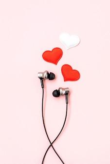Красные и белые сердца с черными наушниками на розовой пастели.