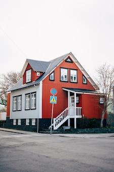 Красно-белый дом с серой крышей на улице в рейкьявике