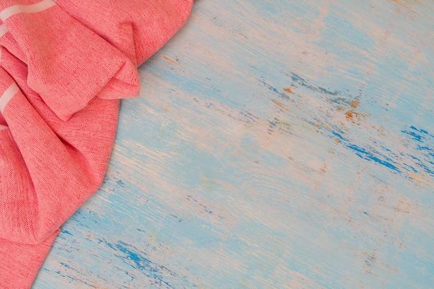 Красное и белое кухонное полотенце лежит на деревянном столе. текстура крашеного дерева. фактурные складки ткани.