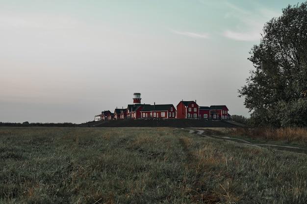 フィールドから見た赤と白の灯台と建物。